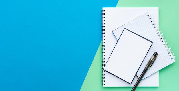 Stos białego spiralnego notatnika i papieru do notatek z czarnym długopisem na niebieskim i wodnym kolorze