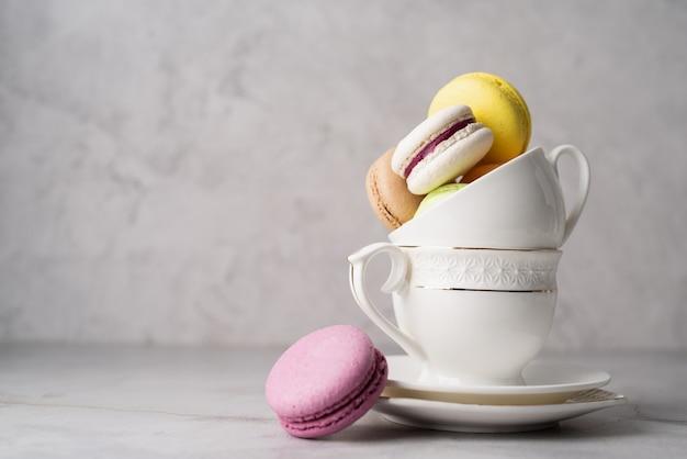 Stos białych filiżanek do kawy wypełnionych makaronikami na krawędzi stołu, białe ceglane ściany w tle