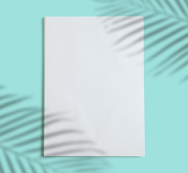 Stos białych folios na turkusowym niebieskim tle, cień roślin