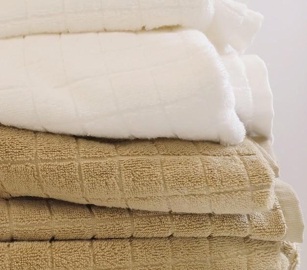 Stos białych i brązowych ręczników kąpielowych z frotte lub bawełny używanych do suszenia lub wycierania ciała.