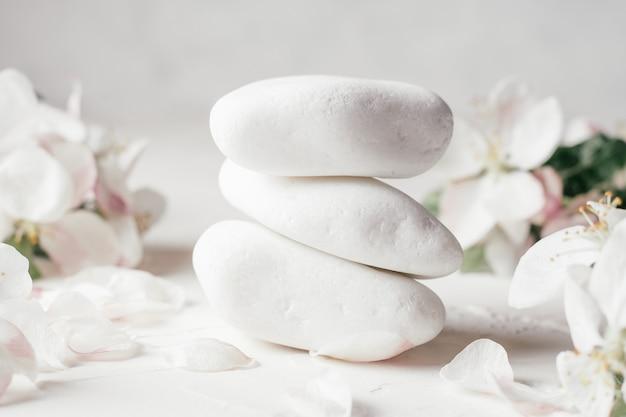 Stos białych kamyczków na jasnej powierzchni tynku, z kwiatami jabłoni