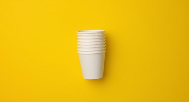 Stos białych kubków papierowych na żółtym tle. koncepcja odrzucania plastiku, zero odpadów