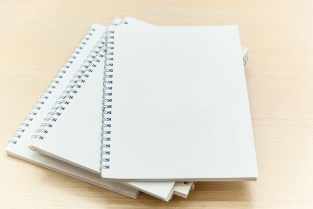 Stos białych notatników na stole konferencyjnym