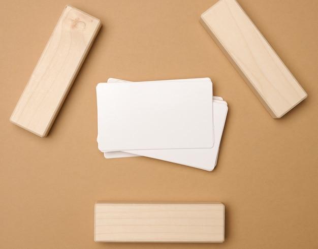Stos białych prostokątnych wizytówek na brązowym tle, branding firmy, adres. widok z góry, leżący na płasko