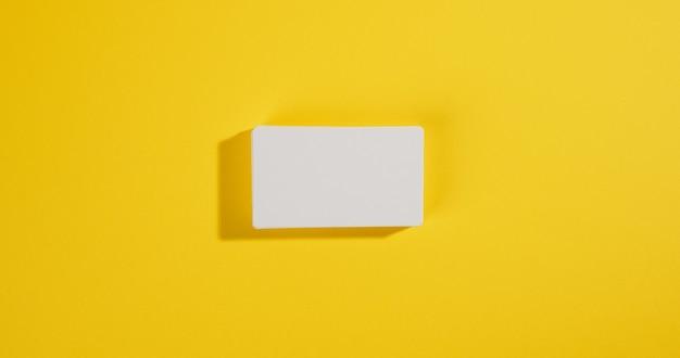 Stos białych prostokątnych wizytówek na żółtej powierzchni, branding firmy, adres. widok z góry, leżący na płasko