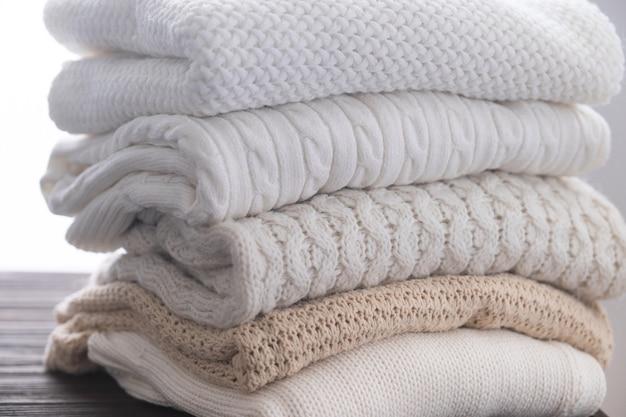 Stos białych, przytulnych swetrów z dzianiny na drewnianym stole