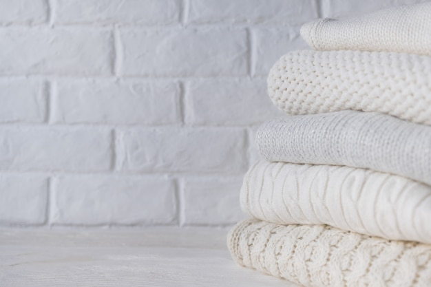 Stos białych przytulnych swetrów z dzianiny na tle białej cegły ściany.