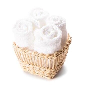 Stos białych ręczników spa w izolowanym koszu