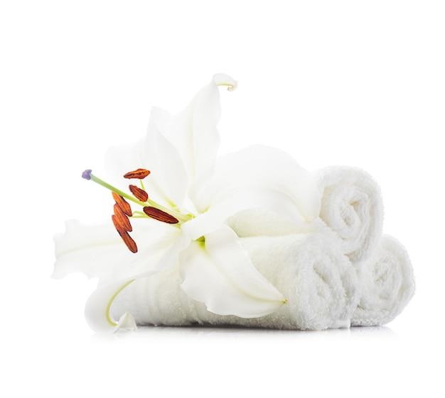 Stos białych ręczników spa z kwiatem lilii na białym tle