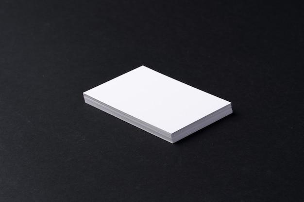 Stos białych wizytówek na czarnym tle