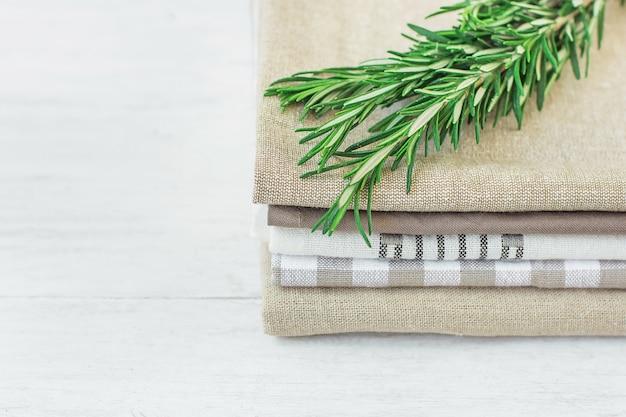 Stos bielizny ręcznikowej i bawełnianej serwetki świeża gałązka rozmarynu na stole z białego drewna