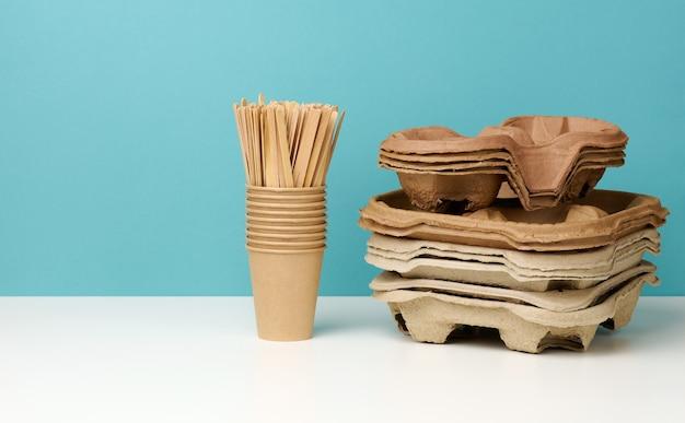 Stos brązowych jednorazowych kubków papierowych i stojak na białym stole, niebieskim tle. przybory do napojów na wynos, zero waste