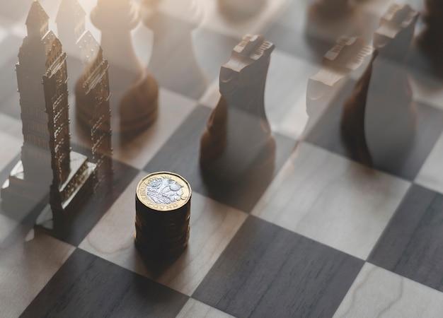 Stos brytyjskich monet funtowych z podwójną ekspozycją pamiątki z wieży big ben z szachami drewnianego rycerza na planszy.