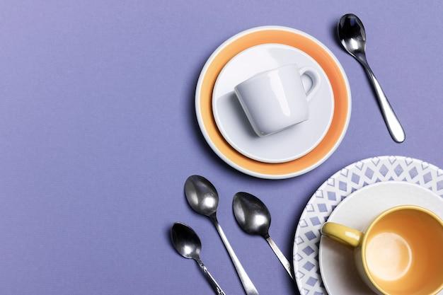 Stos ceramicznych talerzy, filiżanek do espresso, kawy lub herbaty z ozdobami. grupa małych łyżeczek do herbaty. koncepcja serwowania w pastelowych kolorach
