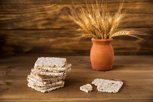 Stos chrupkiego chleba chrupkiego z kłosami pszenicy w wazonie na brązowym tle drewnianych z bliska z miejsca na kopię.