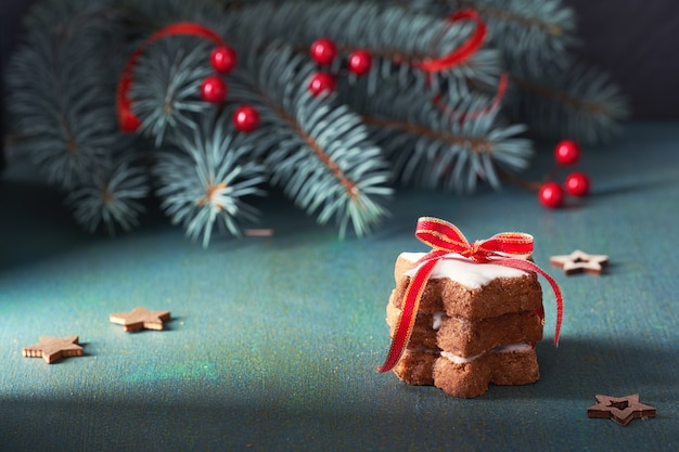 Stos ciasteczka świąteczne gwiazdki związane rudą czerwoną wstążką na zielony i czerwony świąteczny stół z zielonymi gałązkami jodły