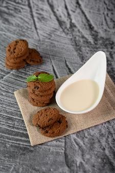 Stos ciastek i łyżka mleka na szmatce na drewnianym stole