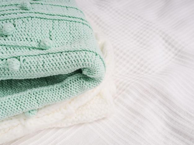 Stos ciepłych dzianin na białym łóżku. przytulne ubrania. koncepcja gospodarstwa domowego. złożone dzianiny białe.