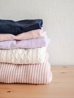Stos ciepłych dzianych wełnianych swetrów w pastelowych odcieniach i granatowy na drewnianym stole