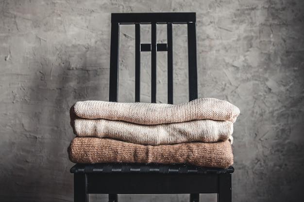 Stos ciepłych, przytulnych swetrów z dzianiny na krześle przy szarej ścianie. koncepcja jesień, zima.