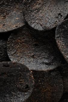 Stos czarnych chipsów ziemniaczanych na betonowym stole niezwykłe frytki