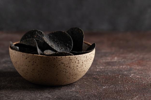 Stos czarnych chipsów ziemniaczanych w ceramicznej misce na betonowym stole z miejsca na kopię niezwykłe frytki
