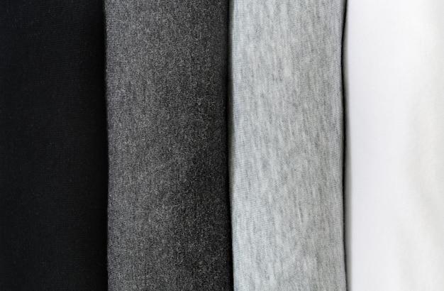 Stos czarnych, szarych i białych koszulek