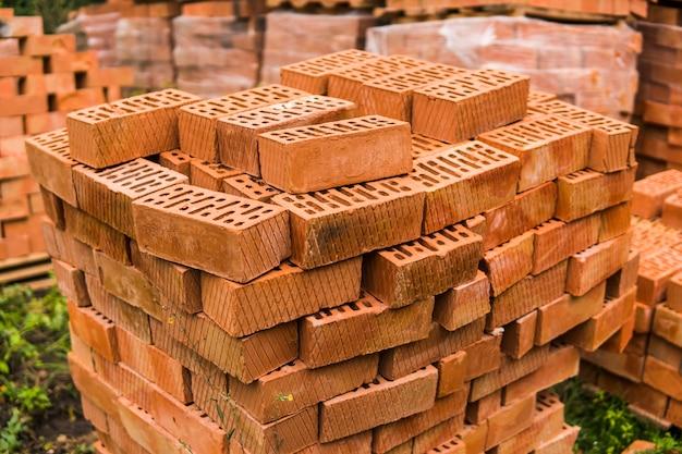 Stos czerwonej cegły dla budowy. cegły budowlane zwykłej jakości ułożone w stos i gotowe do użycia.