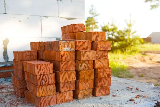 Stos czerwonych cegieł na budowie. materiały budowlane, dostawa, magazyn. skopiuj miejsce