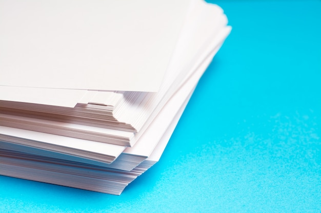 Stos czystego białego papieru na stole na niebieskim tle. puste strony gotowe do drukowania i pisania.