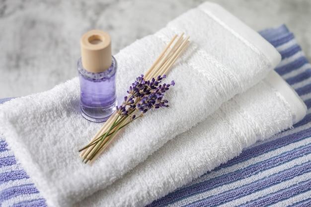 Stos czystych miękkich ręczników z bukietem lawendy i odświeżacza powietrza w kolorze jasnoszarym.