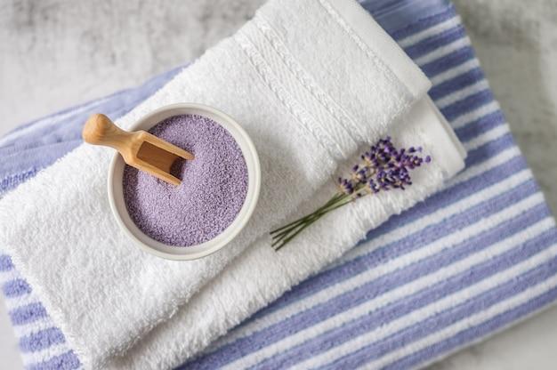Stos czystych miękkich ręczników z bukietem lawendy i soli do kąpieli w kolorze jasnoszarym.