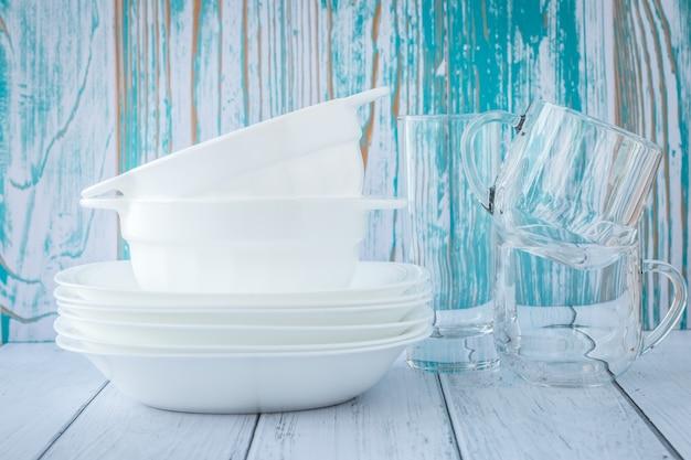 Stos czystych naczyń na ścianie drewna. ceramiczne białe talerze i szklanki.