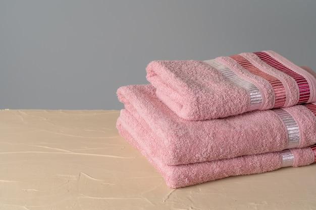 Stos czystych nowych ręczników na szarej ścianie