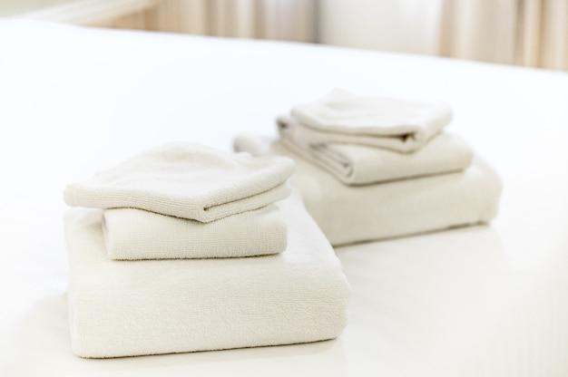 Stos czystych ręczników na łóżku w hotelu.