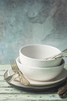 Stos czystych talerzy ze sztućcami na wierzchu na drewnianym stole. pastelowe odcienie.