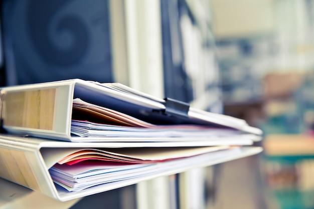 Stos dokumentów z czarnymi klipami w folderach układa się w stos.