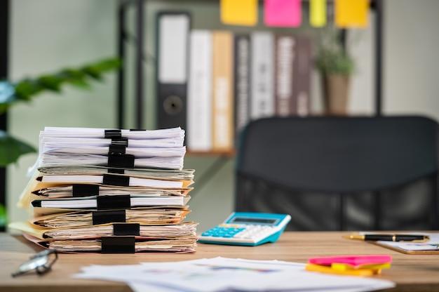 Stos dokumentów z folderem spinacz umieszczony na biurku w biurze firmy.