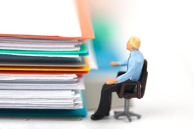 Stos dokumentów z miniaturowym biznesmenem na białym tle