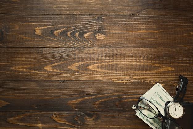 Stos dolarów amerykańskich i zegarek na ciemnym drewnianym tle