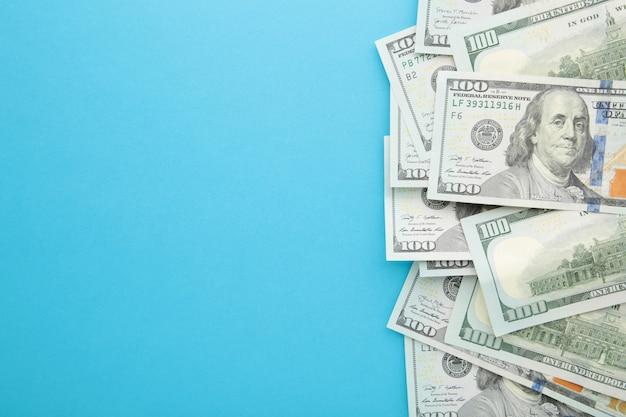 Stos dolarów na niebieskim tle