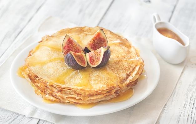 Stos domowych naleśników ze świeżą figą i słodką polewą na białym talerzu