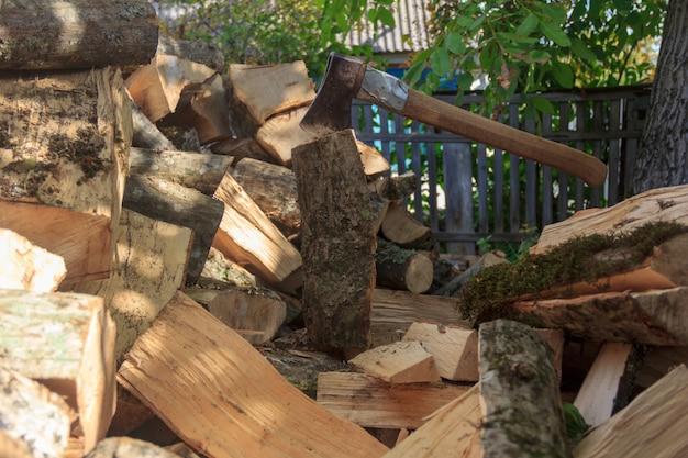 Stos drewna i siekiera utknęły w pniu