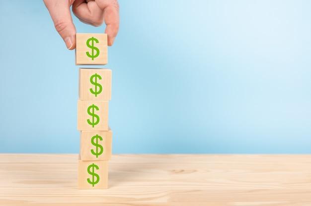 Stos drewnianej kostki ze znakiem dolara na stole, niebieskie tło. skopiuj miejsce. proces rozwoju firmy