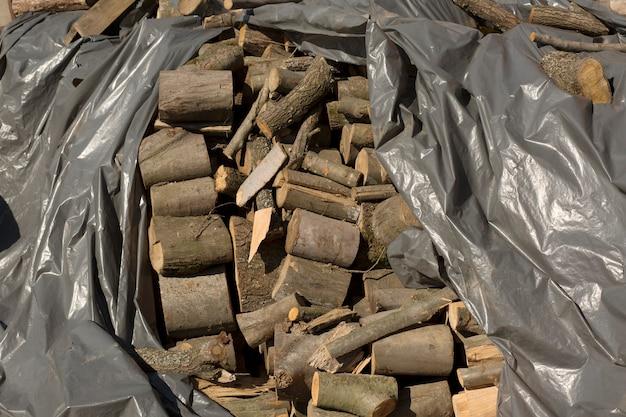 Stos drewnianych bali pokrytych polietylenem na placu budowy