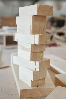 Stos drewnianych cegieł gotowych do wykorzystania w produkcji mebli stojących na stole warsztatowym nowoczesnego pracownika fabryki