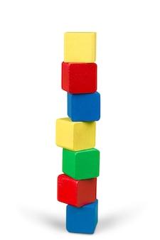 Stos drewnianych klocków zabawek, wieża pustych kostek wielokolorowych pudełek na białym tle