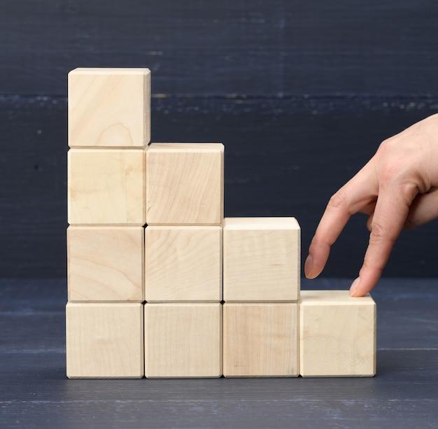 Stos drewnianych kostek 6 palce osoby wspinają się po schodach