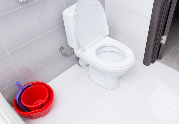 Stos dwóch czerwonych wiader do sprzątania z szufelką obok otwartej łazienki w pokoju hotelowym z biało-szarymi kafelkami