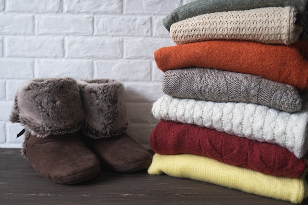 Stos dzianinowych ciepłych ubrań i butów domowych wygodne, przytulne rzeczy do domu jesienna koncepcja